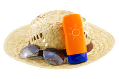 Hat with sunglasses and body lotion on white background Stock Photography