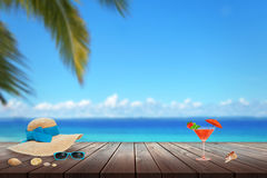 Hat, sunglasses, cocktail, shell on beach table. Beach, sea, palm and blue sky in background. Royalty Free Stock Photo