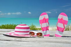 Hat, sunglasses and flip-flops against ocean. Exuma, Bahamas Royalty Free Stock Image