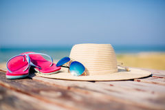 Hat, sunglasses and flip-flops against ocean Stock Photos