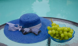 Hat, sunglasses and grape by the swimmimg pool. Woman's hat, sunglasses and grape in glass plate are on table by the swimming pool Royalty Free Stock Photography