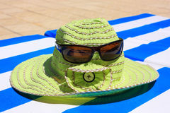 Hat with sunglasses on a lounger. Green hat with sunglasses on a sripped lounger Stock Photo