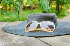 Hat and sunglasses. In park on wood table Royalty Free Stock Images