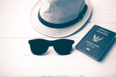 Hat sunglasses and passport vintage style. Hat sunglasses and passport on white table vintage style Royalty Free Stock Photography
