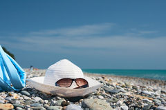 Hat with sunglasses on the pebbles. Hat with sunglasses laying on the pebbles near the sea Royalty Free Stock Image