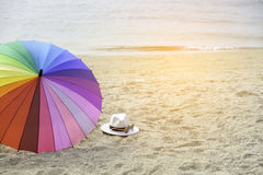 Hat, sunglasses and rainbow colored umbrella on a tropical beach. Pattaya , Thailand Royalty Free Stock Image