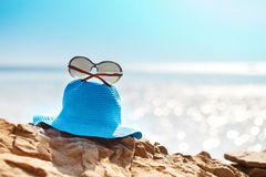 Hat and sunglasses on the rock, clear sea. Vacation concept of travel. Selective focus Royalty Free Stock Photography