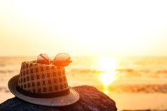 Hat and sunglasses on the rock near the beach and sunset. And water beach Stock Photos