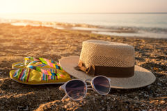 Hat with sunglasses on sand. Flip flops near the sea. The beach is calling. It`s time to relax Royalty Free Stock Photo
