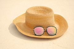 Hat and sunglasses on sand at sea resort. Summer vacation concept Royalty Free Stock Images