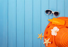 Hat, sunglasses and suntan lotion on wood background colored. Stock Photos