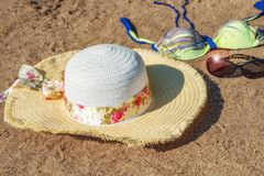 Hat, sunglasses and swimsuit on the sandy beach. Background of women`s accessories on sandy beach. Hat, sunglasses and swimsuit on the sandy beach. Background Royalty Free Stock Photos