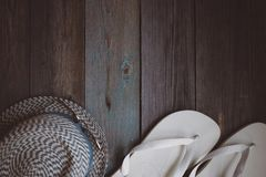 A hat, sunglasses and white flip flops on the wooden table stock photo