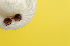 Hat and sunglasses. On yellow background. Summer holiday and travel concept. Copy space background, top view flat lay overhead Royalty Free Stock Photography