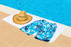 Hat and swimming trunks on towel near swimming pool. Reed hat and swimming trunks on towel near blue fswimming pool Royalty Free Stock Photo