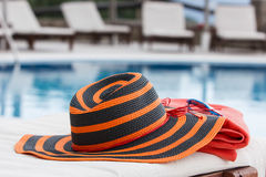 Hat and towel on sunbed. Towel, sunglasses  and hat on the empty sunbed by the resort pool Stock Photography