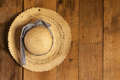 Hat on the wall. Picture of a straw hat with a blue ribbon hanged on a wall made of wood planks Stock Image