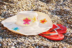 Hat with wide brim and pink flip-flops on beach. Light hat with a wide brim and pink flip-flops on the beach on the pebbles royalty free stock image