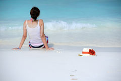 The hat is beside woman sitting on the beach Stock Image