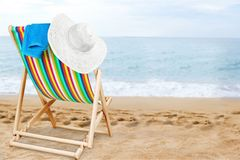 Hat on wooden chaise lounge chair on beach. Wooden chair wood chaise white objects striped royalty free stock photography