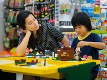 Hat Yai, Songkhla, Tailandia - 3 ottobre 2016: La madre sta esaminando i blocchetti di lego dei giochi da bambini il negozio di L Fotografie Stock Libere da Diritti