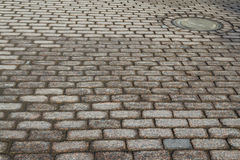 The hatch on the cobbled street. Stock Photography