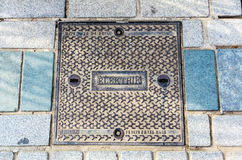 Hatch of sewage on the paving road Royalty Free Stock Image