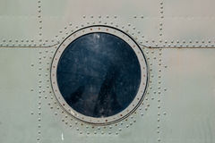 Hatch window of the old aircraft riveted iron plates Stock Images