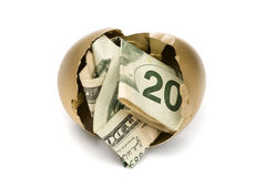 Hatched golden egg with cash. A hatched golden egg reveals some cash for retirement Stock Photo