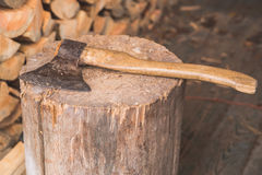 Hatchet thrusted in old stump. Royalty Free Stock Photos