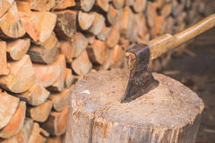 Hatchet thrusted in old stump. Royalty Free Stock Photography