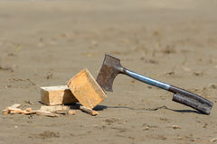 Hatchet and wood chips. On the wet sand Royalty Free Stock Photography