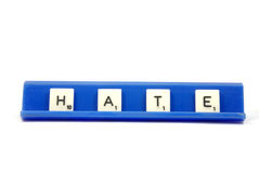 Hate. Scrabble pieces spelling the word HATE on a blue board Stock Image