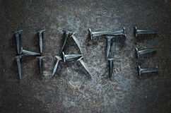 Hate. The word HATE written with studs on a metal background Royalty Free Stock Image