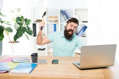 Hate office routine. Man bearded guy headphones office swing hammer on computer. Slow internet connection. Outdated royalty free stock image