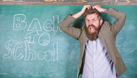 Hate school. Teacher or educator stands near chalkboard with inscription back to school. Teacher unhappy shouting. Hysterically face. Teacher goes mad about stock images