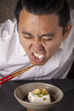 Hate tofu. A man hate to eat Japanese cold tofu on dining table with chopsticks Royalty Free Stock Photos