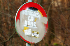 Hateful sign. Karlskrona, Sweden - January 13, 2016: Racist and hateful message saying Refugees go home, painted on a traffic sign with stickers and paint all Royalty Free Stock Image