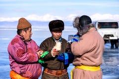 Hatgal, Mongolia, Febrary 23, 2018: gente mongola vestita in abbigliamento tradizionale su un lago congelato Khuvsgul e fotografie stock libere da diritti