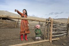 Mongolian nomad kids at their animal closure in a steppe of northern Mongolia. Hatgal, Mongolia, 3rd March 2018: mongolian kids in a steppe of northern Mongolia Stock Image