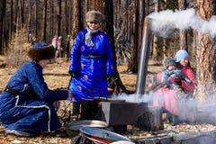 Hatgal, Mongolie, Febrary 23, 2018 : femmes habillées dans le cuisinier traditionnel d'habillement dans la forêt avec le fourneau photo libre de droits