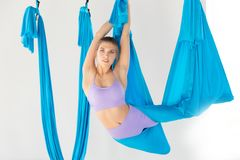 Hatha aero fly yoga concept. Beautiful young female trainer showing stretching exercises on blue hammock in white studio.  royalty free stock image