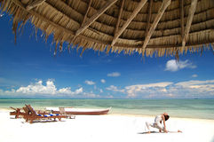 Hatha Yoga. By the beach with blue sky, crystal clear water and sandy beach at a tropical resort Stock Images