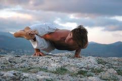 Hatha-yoga: ashtavakrasana. Man doing a ashtavakrasana. Hand standing Stock Photography