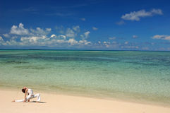 Hatha Yoga by the beach. With blue sky, crystal clear water and sandy beach Stock Images