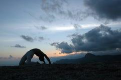 Hatha-yoga: bridge #3. Man doing a bridge. Sunset Royalty Free Stock Photo