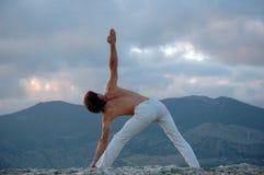 Hatha-yoga: utthita-trikonasana. Man doing a utthita-trikonasana Stock Photos
