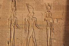 Hathor, Horus and Isis. The Ancient Egyptian gods Hathor, Horus and Isis carved on the side of the Temple of Isis at Philae, Aswan, Egypt stock photography