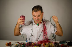 Hating parties. Guy struggling with a mess of party decoration Royalty Free Stock Photos