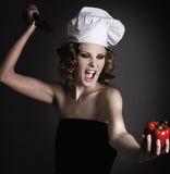 Hating peppers. Beautiful girl  with chef's hat and a scream pointing her knife at a pepper Stock Image